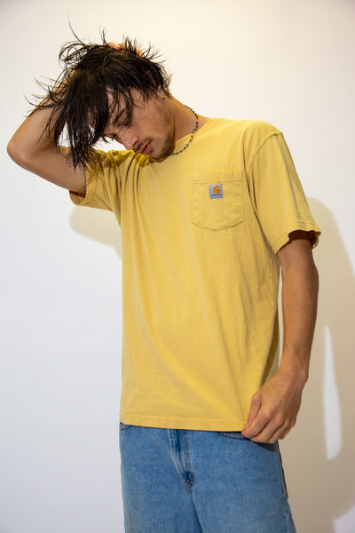 With Carhartt branding on the lil left chest pocket, this tee is mustard yellow.