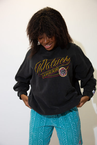 Black in colour, this sweater has a large maroon and yellow appliqué of 'Chicago Wolves' printed across the front with he teams mascot and logo below.