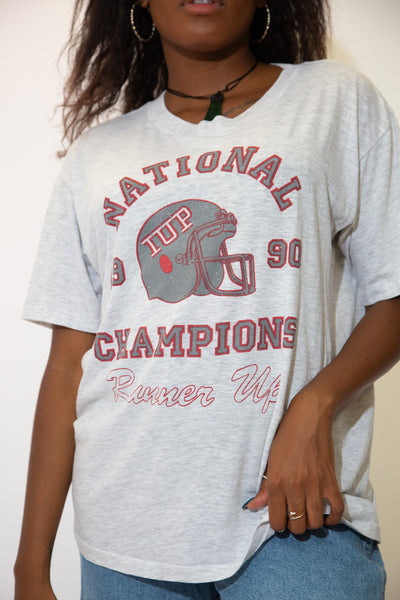 The model is wearing a grey tee that features a sports tee with IUP