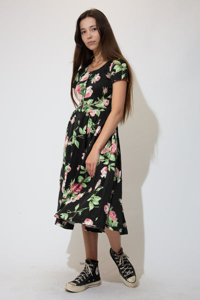 This summer dress is black in colour with a midi-length style and large-print floral design. With buttons down the front and a flowy-styled skirt.