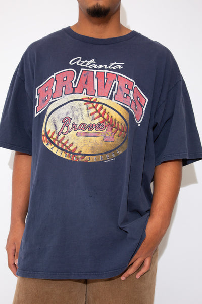 model is wearing a navy tee that features a cracked logo by the atlanta braves