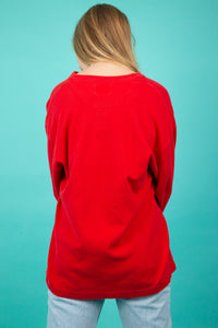 This long-sleeved tee has a thick ribbed texture and is red in colour with metal branded buttons.