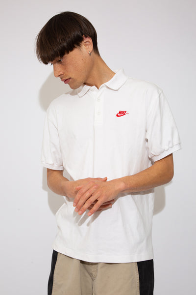 white nike polo with red embroidered tick and text logo on left chest