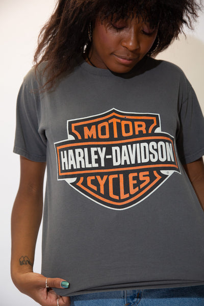 Grey in colour, this tee has the iconic Harley Davidson logo on the front. On the back, an orange and white print of n eagle and motorcycle with 'mile high' printed in white, repping Aurora, Colorado.
