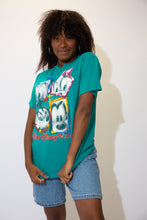 Load image into Gallery viewer, The model is wearing a teal vintage disney tee featuring mickey mouse and the gang on the front!