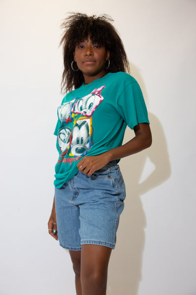 The model is wearing a teal vintage disney tee featuring mickey mouse and the gang on the front!