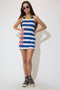 This Coca-Cola dress is blue and white striped with yellow rimming along the neckline and sleeves and finished off with the iconic Coca-Cola logo vertically printed on the right side in red.