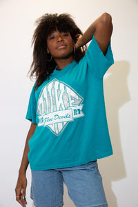 The model is wearing a teal coloured vintage tee showing Dukes mascot the Blue Devils.
