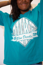 Load image into Gallery viewer, The model is wearing a teal coloured vintage tee showing Dukes mascot the Blue Devils.