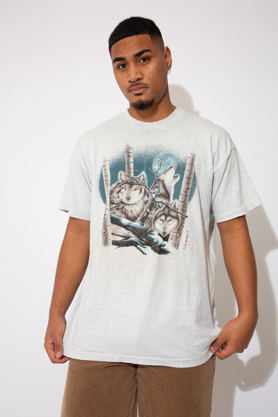 model is wearing a grey tee that features a pack of wolves