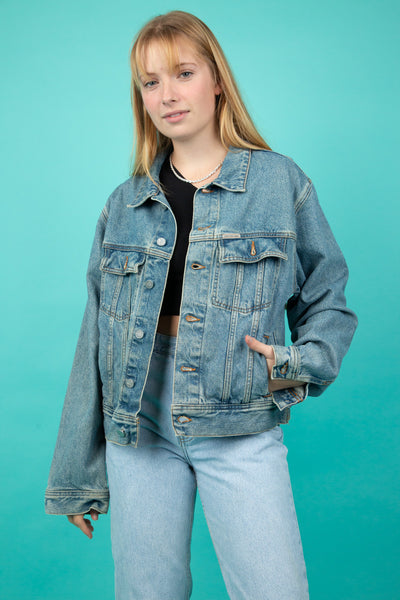 This Calvin Klein denim jacket is a blue mid-wash and has brown stitching. It is branded 'Calvin Klein Jeans' on the left chest pocket and all the buttons.