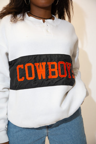 The model is wearing a cowboys sweater that features a applique print on the front