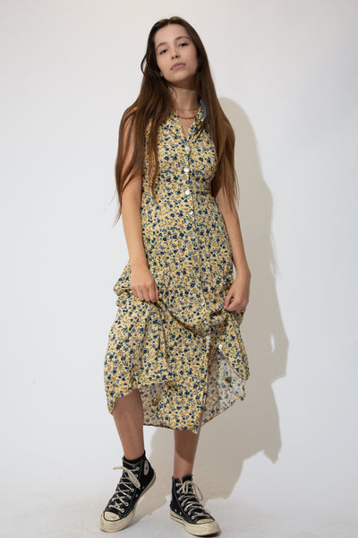 Pale yellow in colour with a blue and grey floral design, buttons all the way down the front, a denim-like collar and a midi-length, flowy fit. Has a tie up back to adjust the size and accentuate the waist.