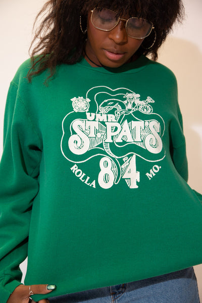 The model is wearing a green sweater that features a white print on the front, the sweaters graphic features a fun St Pats on the front