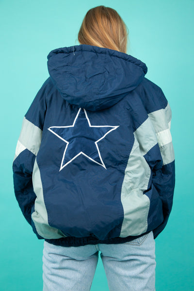 This jacket is blue, white and silver and has circular closing domes, a closing zip and draw strings along the hood. The 'Starter' logo is on the left sleeve and back of the jacket. Has striped arms and the Cowboys logo on the left chest and back.