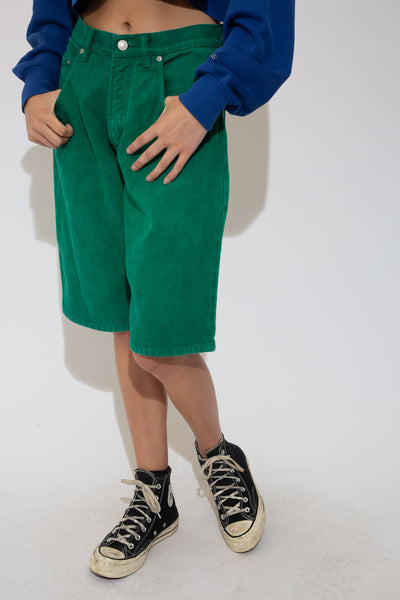 Dark green denim shorts with green stitching and silver buttons and domes in a midi-length style.