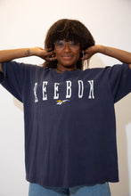 Load image into Gallery viewer, Navy blue single stitch tee with a large, white Reebok spell-out across the front and an embroidered Reebok logo below.