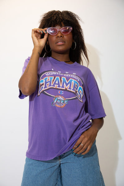 Purple in colour, this tee has 'Midwest Division Champs' printed across the front with 1998, the Champion logo and the Utah Jazz logo.