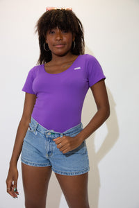 The model is wearing a purple bodysuit made by wrangler