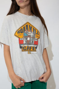 Grey single-stitch tee with a large colour print on the front of a scared looking deer on the front of a car, 'Roadkill Cafe' printed on the front and dated 1992 at the bottom. On the back, a list of funnily named specials.