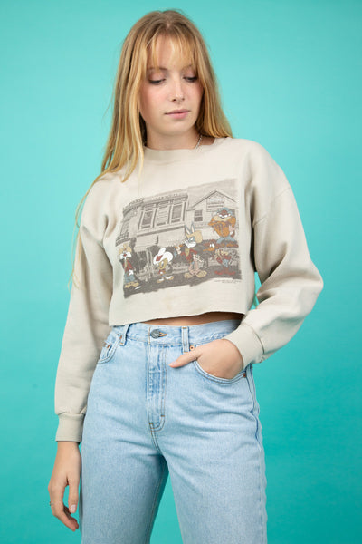 This tan brown sweater is cropped and oversized with the whole Looney gang printed on the front. Dated 1997 at the bottom.
