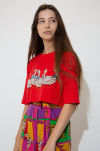 Red single-stitch tee with three quarter length sleeves and a print of five ducks in a row on the front. Cropped to keep it cute.