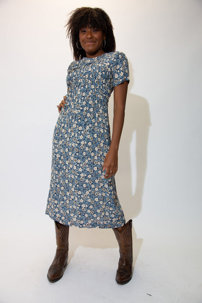 With its midi-length style, floral pattern, pleated chest, shoulder padding and adjustable synched waist, the blue Helena Dress is a vintage must-have.