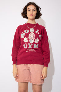 Oversized, maroon red sweater with 'World Gym' printed in grey and a print of a gorilla lifting weights on the front. Repping Walzem San Antonio, Texas. Print reversed on back.