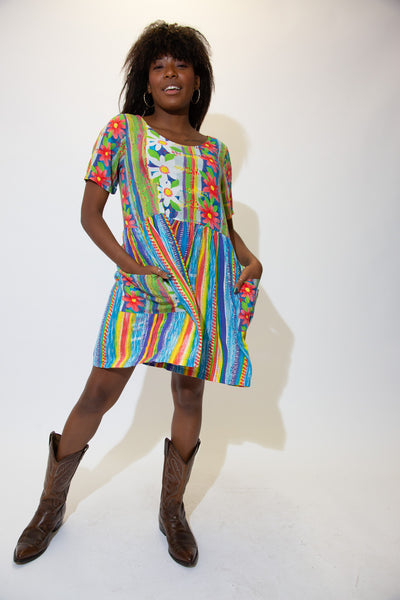 Brightly coloured in linear patterns and flowers, this dress cuts at the knee, has a flattering crew-neck neckline and pockets!!!