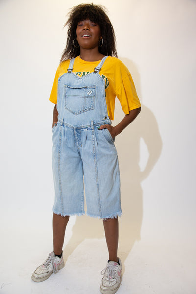 the model wears a light washed pair of denim overalls