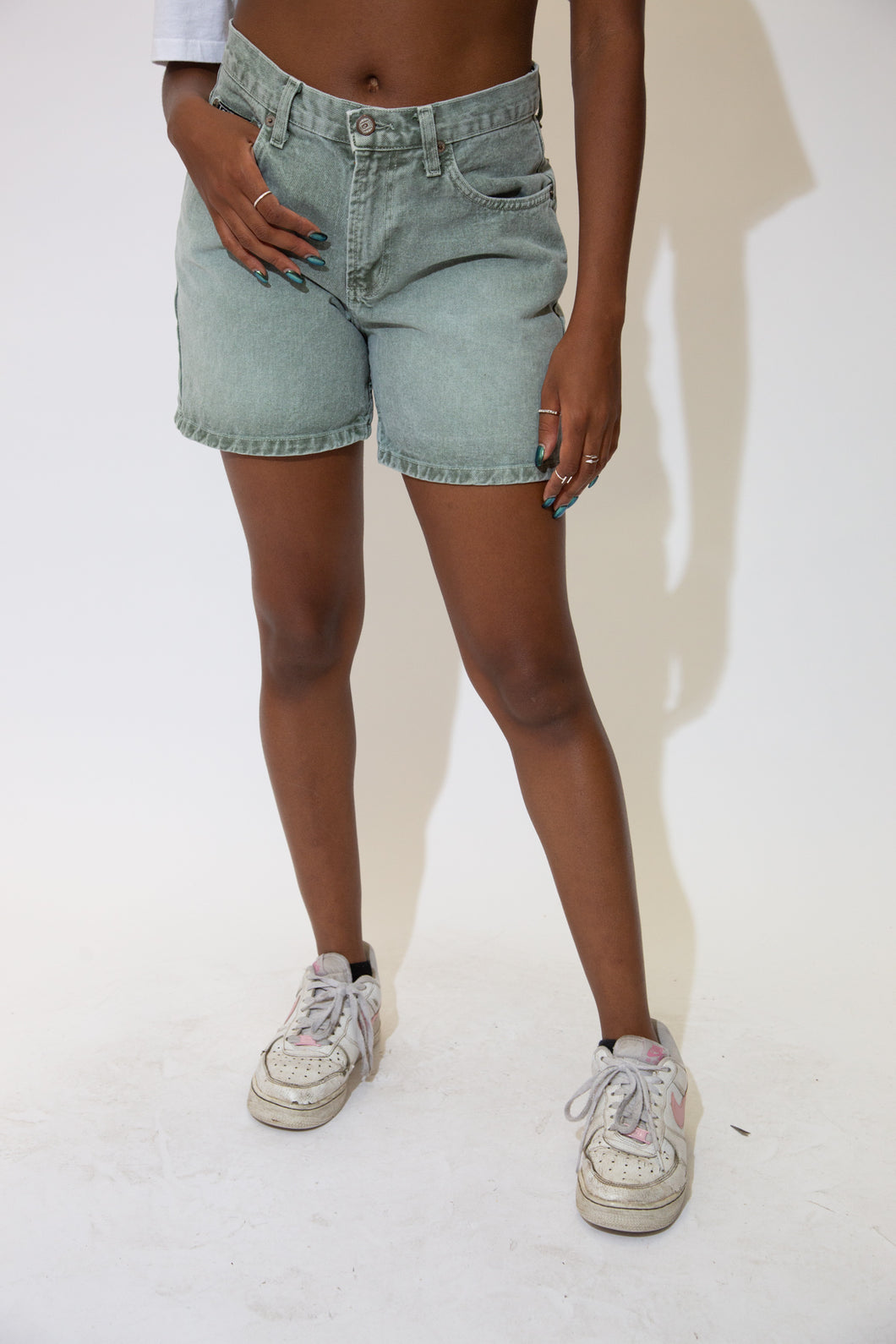Light-wash green, these denim shorts have white stitching, pentagon shaped back pockets and branding on the button, front pocket and back waistline.