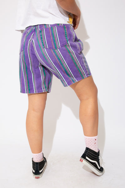 These shorts are purple with vertical green, white and brown stripes with pockets on the front and back. Knee length and finished off with purple stitching and bronze coloured buttons.
