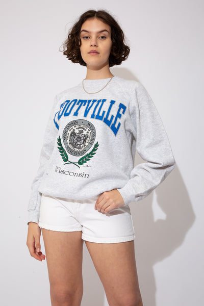 This oversized jumper is grey in colour with Footville printed in blue. Below, the Wisconsin emblem and Wisconsin printed in black. Dated 1992.
