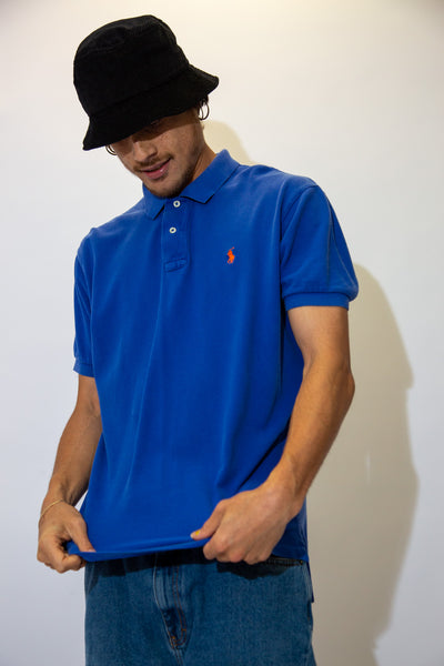 Cornflower blue in a textured material, this polo style tee has an orange embroidered Ralph Lauren logo on the left chest.
