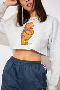 model is wearing a white denim jacket, that features brass buttons going down. This jacket fits oversized on the model.is wearing a grey cropped sweater featuring a cute Winnie the Pooh