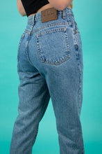Load image into Gallery viewer, These jeans are a Mid-Wash blue with brown stitching and straight legs. With a brown leather 'Calvin Klein' plaque at the back and branding on the pocket and button, these pants are a lucky find.
