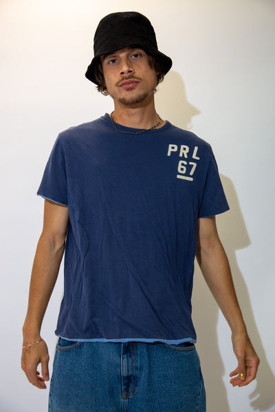 This reversible Ralph Lauren Tee is light blue with a yellow embroidered logo on the left chest, and turned inside out, is navy blue with PRL 67 embroidered on the left chest.