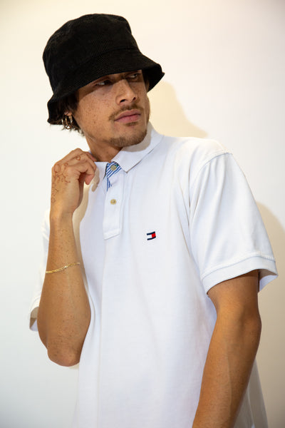 White in colour in a ribbed material, this polo-style tee has a blue and white striped detail on the collar and the iconic Tommy Hilfiger logo embroidered on the left chest.
