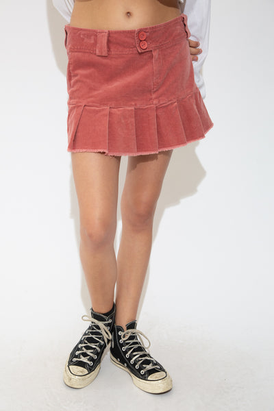 With its pink colour and soft corduroy feel, this tennis style skirt has a pleated bottom, frayed rims, zip and double button closures and a thick belt loop.