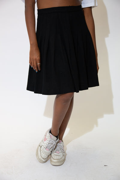 This black, wool skirt is in a pleated style with an accentuated waist.