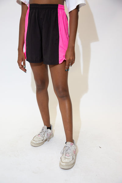 the model wears black nylon shorts with pink panel details