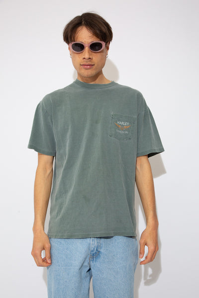 model is wearing a green tee that features the harley logo on the left pocket as well as a massive back print that features Florida.