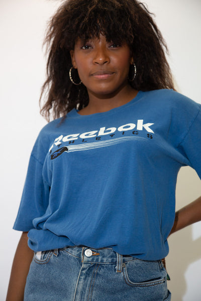 the model wears a blue tee with a reebok spell-out on the front