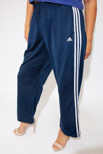 Load image into Gallery viewer, Navy blue, with the staple three vertical white stripes on the sides, these trackies have an inner-drawstring around the waist and a slightly flared leg. Finished off with the Adidas logo on the left leg.