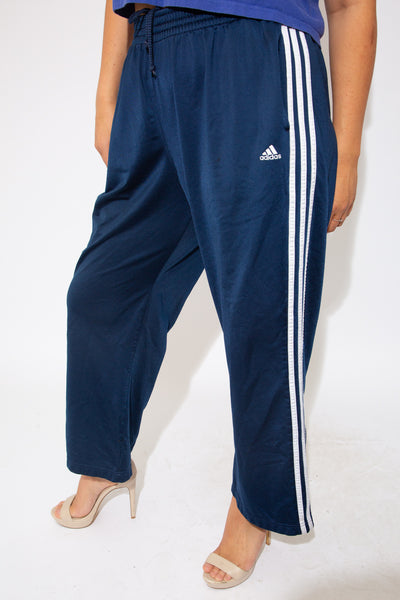 Navy blue, with the staple three vertical white stripes on the sides, these trackies have an inner-drawstring around the waist and a slightly flared leg. Finished off with the Adidas logo on the left leg.