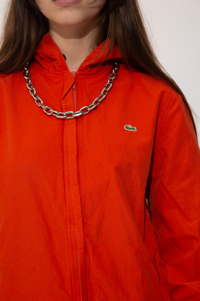 This jacket is burnt orange colour with a hard, sturdy material shell. Finished off with elasticated sleeves, pockets with dome closures' closing zip, an adjustable hood and waistline and branding on the left chest.