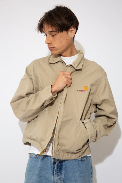 model is wearing a khaki coloured jacket that features a Carharrt logo on the left chest