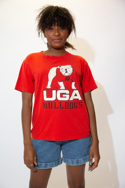 the model wears a red tee with a uga bulldogs spellout on the front