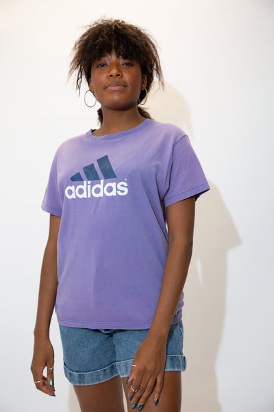 the model wears a purple tee with a large adidas logo graphic on the front