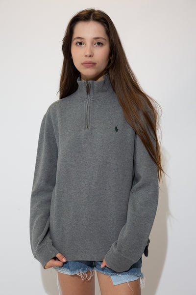 Dark grey in colour with a soft cotton feel and a turtle neck design, this jumper is fitted with a quarter zip made of brown leather and is finished off with dark green branding on the left chest.